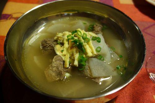 Versez le bouillon avec la viande dans un bol et décorez d'oeuf et de ciboule