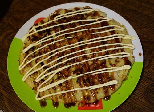 Décorez l'Okonomiyaki avec la mayonnaise et la sauce